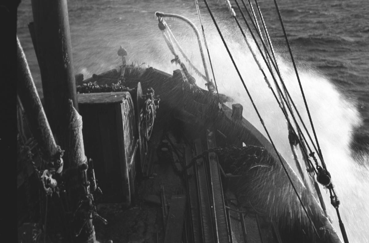 """Sjøsprøy mot baugen på en båt. Fartøyet kan være skøyta """"Knut"""", som ble brukt som lokalbåt."""