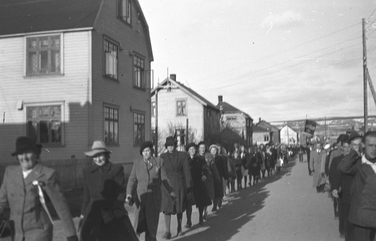 Et tog går gjennom ytrebyen i Vadsø. Det er så lite norske flagg i toget at det er tvilsomt at det er 17. mai-tog. Erling Stålsetts hus ses til venstre på bildet og nederst til venstre ses fru Skogsholm.