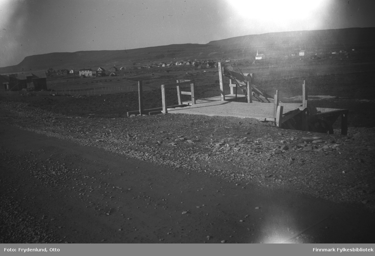 Ved veien til Vestre Jakobselv var det satt opp en trerampe med nedgang til noe som ser ut som utstyr til solding av sand. Kirka og andre hus i bygda sees i bakgrunnen