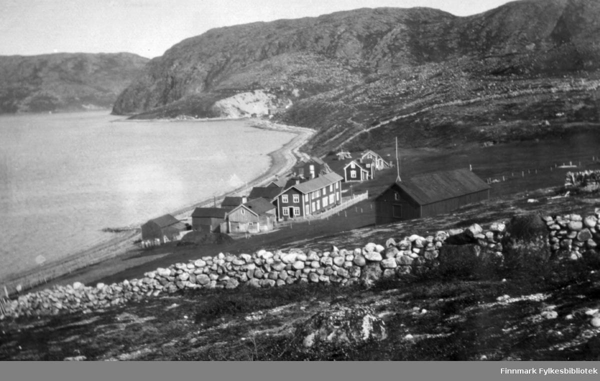 Oversiktsbilde over familien Gunnaris hus og kulturlandskapet rundt Bugøyfjord. Det øverste huset er høysjå. Ellers ser vi fra venstre ved vannet sjøbod, ovenfor den fjøs med stall, sauefjøs og hønsehus. I midten ser vi hovedhuset og nest lengst til høgre Rauhala. Ca.1915-1920.