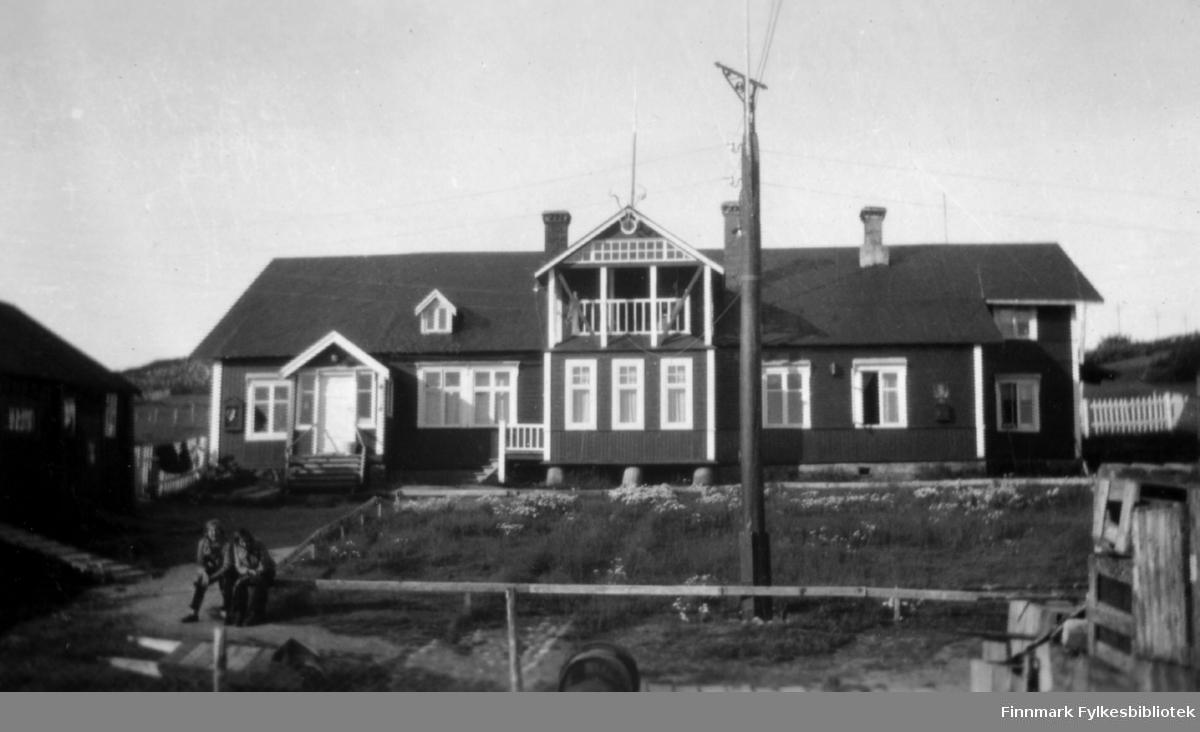 Ella Gunnari og Ruth Grønvigh sitter foran familien Gunnaris hus i Bugøyfjord.