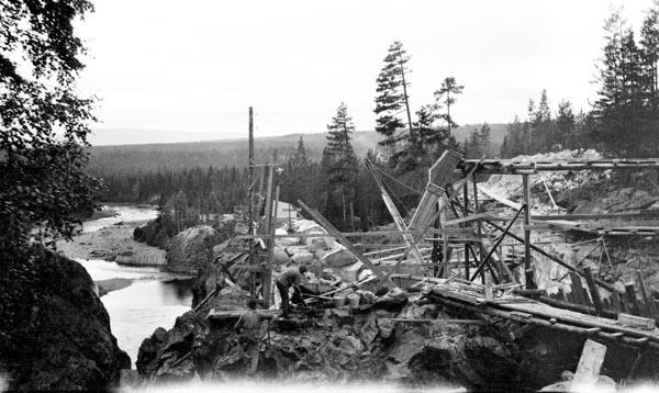 Sprengings- og forskalingsarbeid i forbindelse med kraftutbygginga ved Osfallet i elva Søndre Osa i Åmot kommune i Hedmark, antakelig sommeren 1913.  Fotografiet synes å være tatt fra den bergnabben elva passerte, og som bidro til at man her hadde en samlet fallhøyde på 25,5 meter.  I forgrunnen kan det synes som om man har minert et nytt far for overløpsvann og tømmer i det nevnte berget.  Sjølve kraftstasjonen skulle reises på flata nedenfor.  Anleggsarbeidene pågikk i 1913 og fram til oktober 1914, da anlegget ble satt i drift.  Om lag halvannet år seinere, den 10. mai 1914, forårsaket en brå og kraftig vårflom et dambrudd som fikk Søndre Osa til å bryte gjennom nordre damarm og danne et nytt elveløp på nordsida av det opprinnelige.  Dette dambruddet forårsaket store skader og betydelige økonomiske tap, særlig for Åmot kommune.  Mer informasjon om om kraftutbygginga ved Osfallet og det påfølgende dambruddet finnes under fanen «Opplysninger».