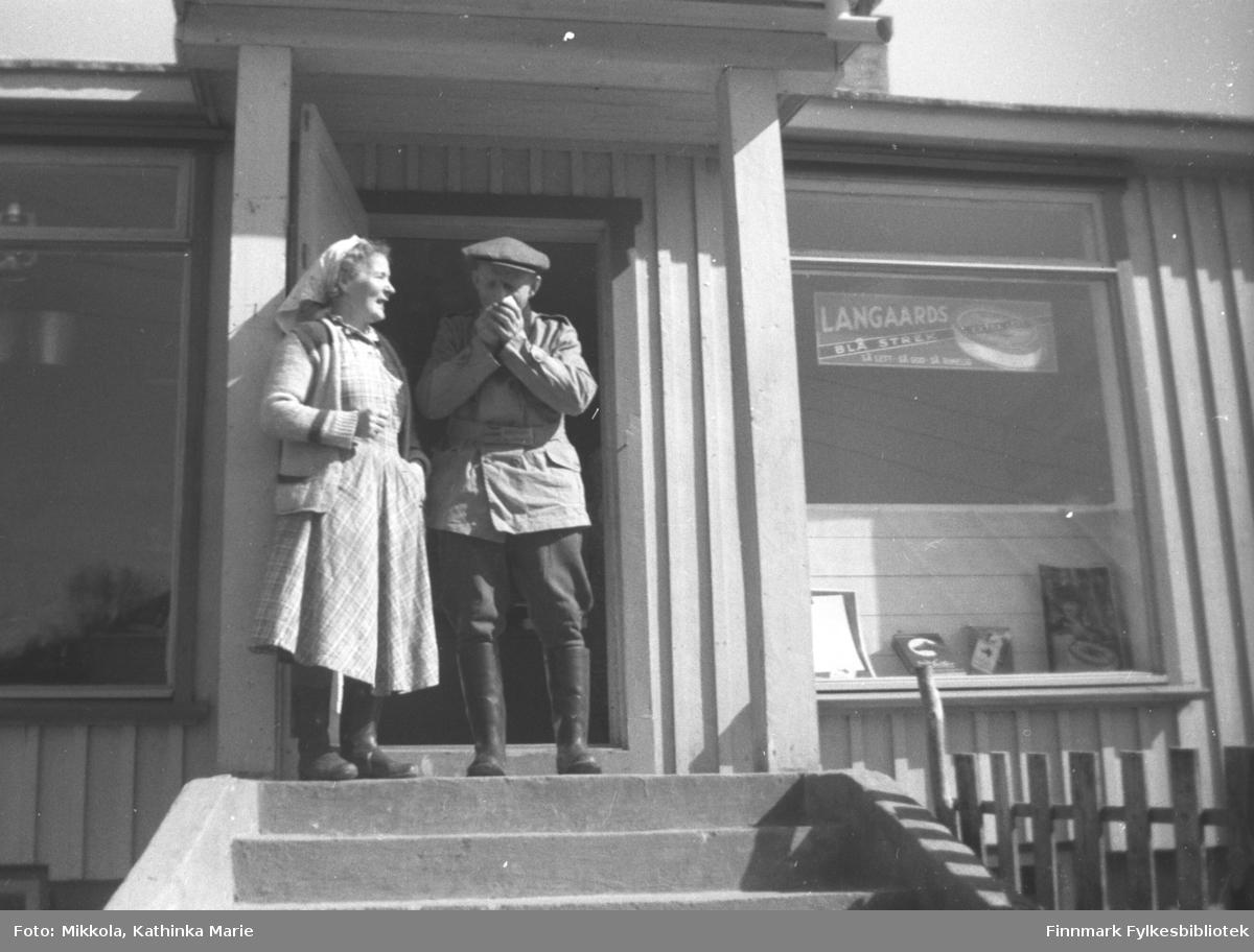 Astrid Mikkola og Mathis Jankila på trappa til Aksel Konrad Mikkolas butikk i Neiden, antakelig 1960-tallet. Butikken lå ved kirka i Neiden