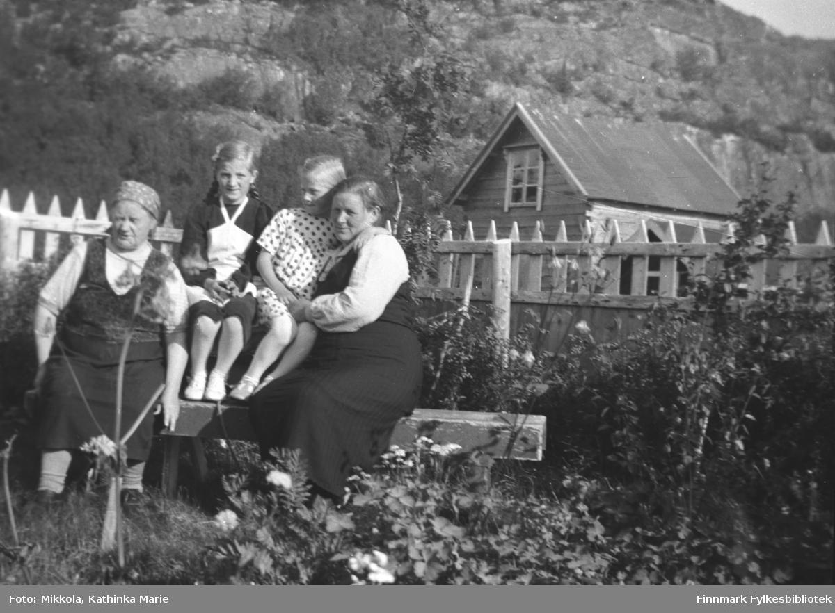 Hagebenken på Mikkelsnes. Fra venstre: Ida Angel, Astrid og Herlaug Mikkola og en ukjent kvinne på besøk fra Vadsø. I bakgrunnen ser vi melkebua på gården