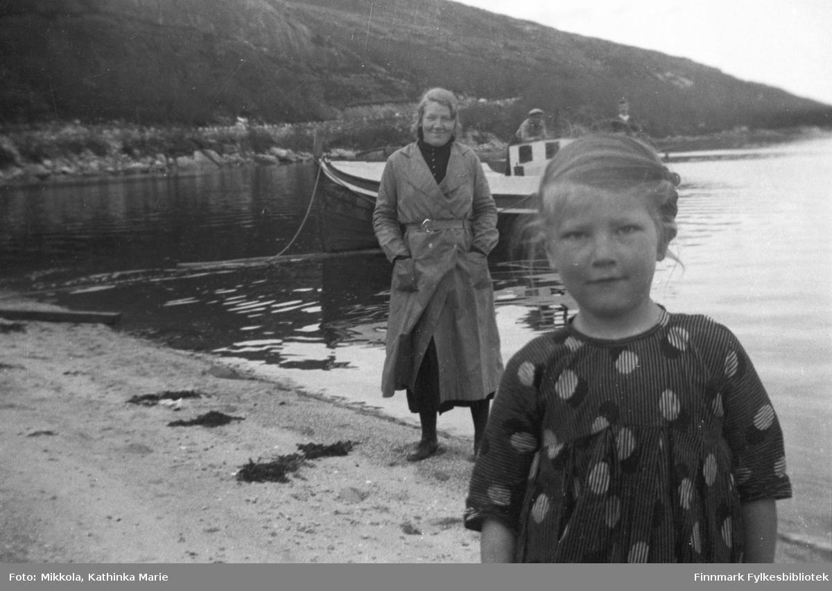 På stranda ved Mikkelsnes. Ingrid Mikkola nærmest kamera, hennes søster Synnøve står litt lenger bak. På sjøen en liten motorbåt med to menn ombord. Det ser ut til at havet ligger blikkstille