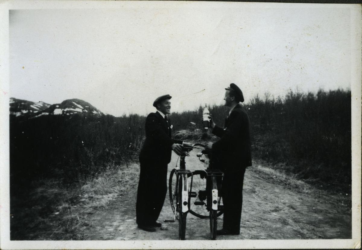 To menn står med hver sin sykkel på en grusvei. Mannen til venstre er Alf Larsen, og mannen til høyre trolig Jakob Reeberg. Jakob holder på en flaske av noe slag. Begge er kledd i jakker, luer og bukser. Begge var arbeidere på skiferbruddet i Friarfjord.