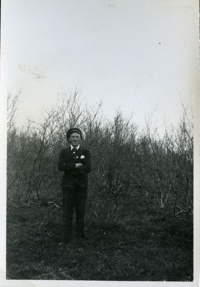 Et fotografi av en mann som muligens kan være Alf Larsen. Alf var arbeider på skiferbruddet i Friarfjord. Her er han kledd i lue, jakke, bukse og slips. Han står foran noen trær.