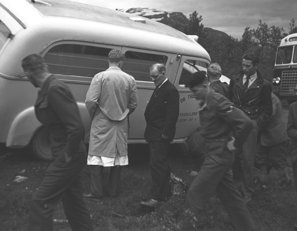 """Bilen på skrå er en sykebil/ambulanse: De bakre siderutene har matt glass og nest nederste linje på døra har tekst """"sykebilene"""". Teksten øverst """"og tro.."""" er Troms eller Tromsø,  nederst et telefonnummer 416 A. Umulig å si noe om bilmerke, men den ser ut til å ha delt frontrute, som kan indikere tidlig etterkrigsmodell - eller sen førkrigs. Mann med ryggen til har kanskje legefrakk under kappa. De to nærmest har militæruniform, den bakerste er visekorporal."""