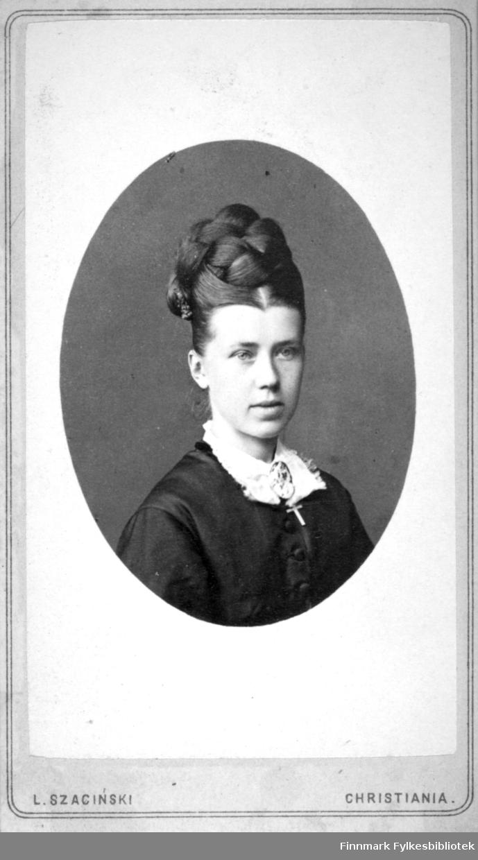 Portrett av en kvinne med oppsatt hår og iført en mørk bluse med hvit krage. Hun har en brosje festet i halsen. Portrettet er tatt hos kgl. hoffotograf L. Szacinski.