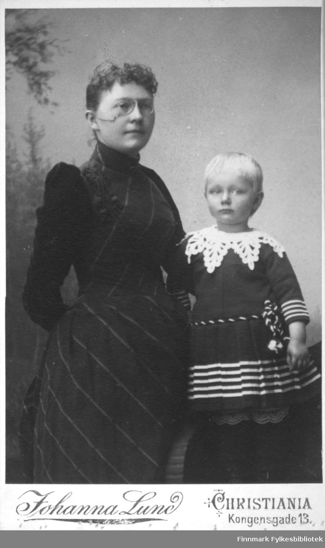Portrett av en kvinne og et barn. Kvinnen har en mørk kjole på seg og lorgnetter på nesen. Barnet har en mørk drakt/kjole med striper rundt livet og håndleddene. En heklet krage ligger rundt halsen.