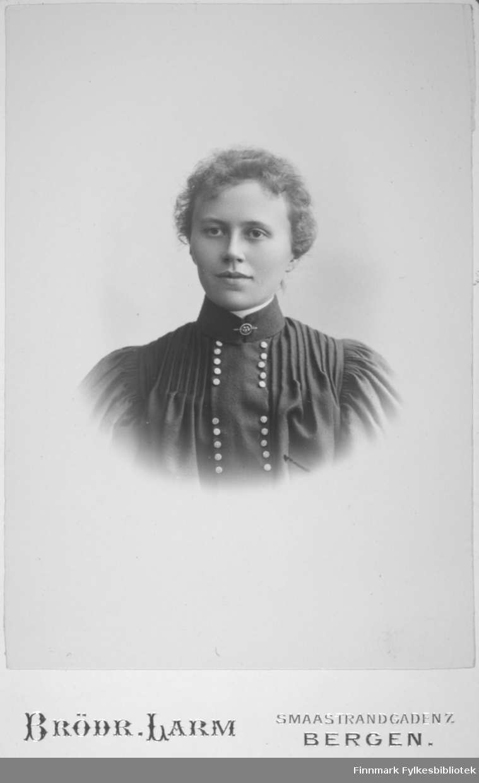 Portrett av en dame i mørk kjole. Lyse knapper går tett i tett fra halsen og nedover brystet. Portrettet er tatt hos Brødrene Larm i Bergen.