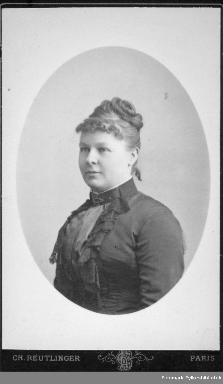 Portrett av en dame med oppsatt hår. Hun har en mørk bluse med mønster og høy krage i halsen. Portrettet er tatt hos fotograf Ch. Reutlinger i Paris.