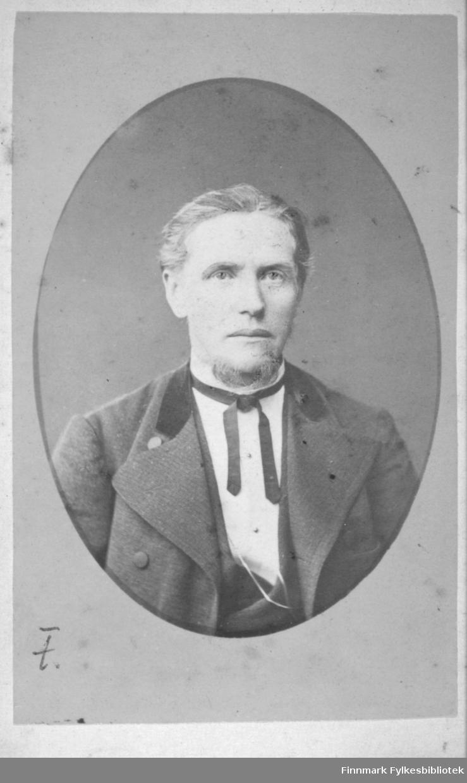 Portrett av farfar Buck. Han har en mørk dressjakke, mørk vest og hvit skjorte på seg. En sort sløyfe går rundt halsen.