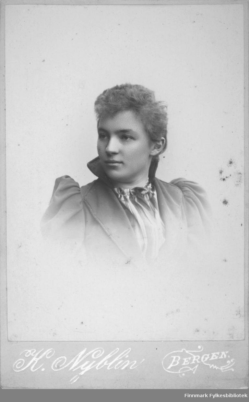 Portrett av en kvinne iført en mørk overdel med skulderputer og en litt lysere bluse under.