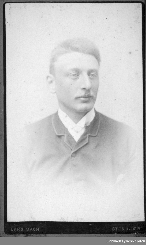 Portrett av en mann iført en ganske mørk jakke  med hvit skjorte under.