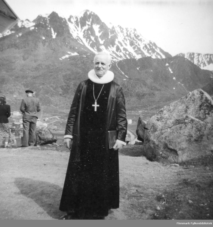 Biskop Wollert Krohn-Hansen iført prestekjole og kappe med en stor hvit prestekrage, står på kirkebakken i forbindelse med innvielsen av kirka. Et kors henger i en kjede rundt halsen hans og i hånda har han en en bok. Området der han står er flatt med grusdekke. Helt til venstre står en dame med prikket skjørt, mørk jakke og hvite sko. Ved siden av henne står en mann i ensfarget dress og hatt på hodet. Oppe til venstre ses en flik av vindskibordet til kirka. Store steiner står i utkanten av det flate partiet der presten står. I bakgrunne ses høye fjell med taggete topper med snøflekker. Ved foten av fjellet står noen bygninger og en liten del av en grusvei ses rett bak armen til presten.