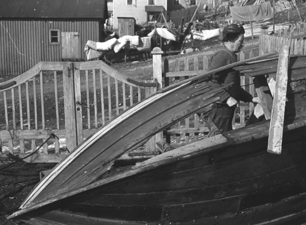 En robåt har fått sprengt et hull i siden av en tysk håndgranat.. Alfred Amundsen er i gang med å fikse båten i hagen hos familien Hauge i Nyborgveien.