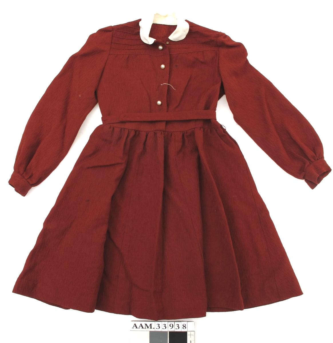 Barnekjole med lange ermer av rødt bomullstoff. Hvit krave. Knepping med trykknapper foran. Hvite pynteknapper. Belte med trykknapper.