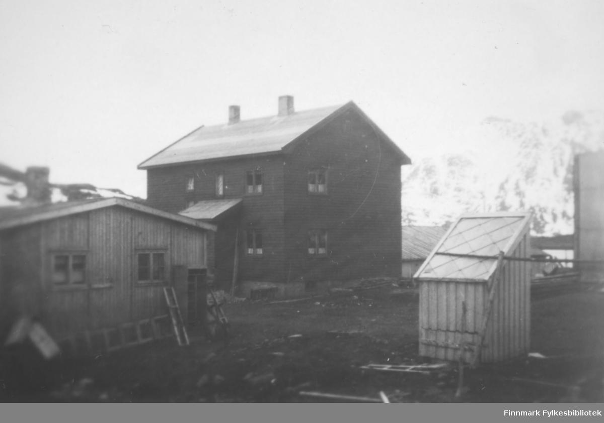 Et stort, mørkmalt hus står på et ganske flatt område. Huset har skiferdekke på taket og to skorsteiner ses på taket. Et lite vindfang er bygd på langveggen. Huset har seks to-delte vinduer som ses. Til venstre på bildet står et mindre hus. Det har en skorstein på taket, to to-delte vinduer på røstveggen og en del saker står inntil veggen, bl.a en stige. Til høyre på bildet står et lite bygg. Det har stående panel og skiferdekke på taket. Mellom det og det store huset ses det skiferdekte taket ses det skiferdekte taket til et hus. Helt til høyre på bildet ses en tank/silo og en svært liten del av fjorden ses ved siden av den. Terrenget rundt bygningene består stort sett av jord. I bakgrunnen ses fjell med snøflekker på.