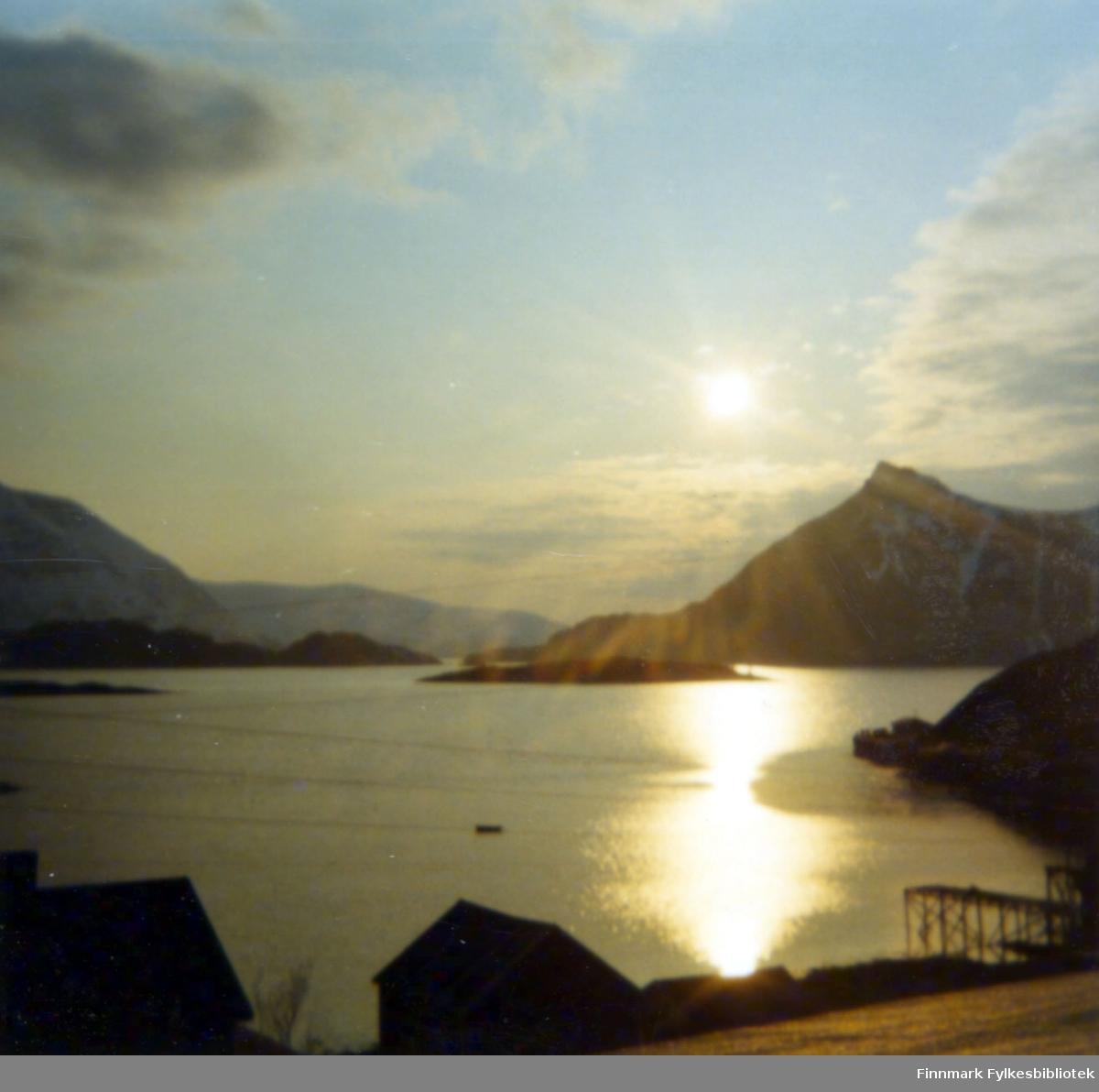 Kveldssol over Bergsfjord. Stort sett blå himmel, men spredte skyer kan ses. Litt vindgråe på sjøen og en båt er midt på bildet. Siluettene av to bygg ses nederst på bildet og nede til høyre står en trekai delvis ute i sjøen. Bak dem skrå et gressdekt jorde ned mot fjæra og over bygningene går tre el-ledninger i luftspenn. Et nes stikker ut i sjøen til høyre for kaia. Bakerst, til høyre på bildet ligger Bukkeskinnfjell med den karakteristiske toppen. Foran fjellet ligger Lyktholmen. Til venstre på bildet stikker et lite nes, som muligens er Langholme, ut i sjøen og bak den ligger sannsynligvis Marøya. Fjellet bakerst i bildet til venster er mest sannsynlig Svartberget.
