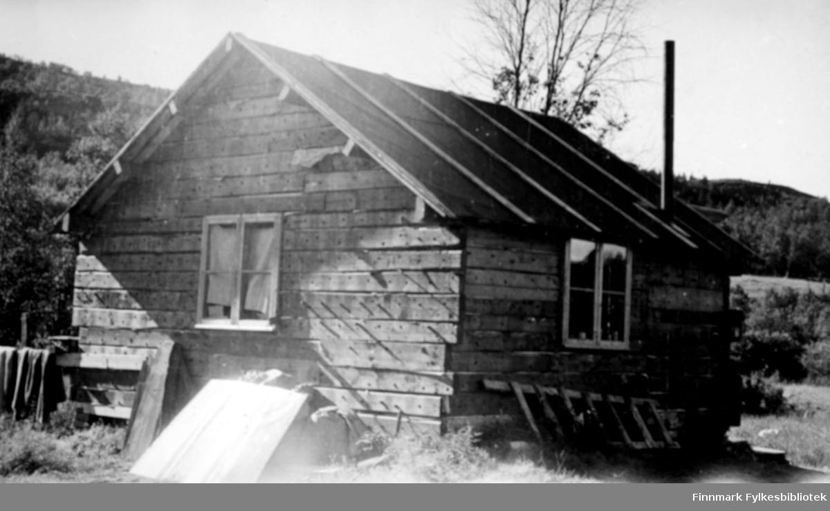 Flyplank-kåken på Gamnes. En onkel av Karen Kristine Jakobsen bygde dette huset til familien da de kom tilbake i 1946 etter evakueringen. Flyplassen som tyskerne bygde i Alta under krigen var bygd av tykke planker. Disse plankene var et kjærkommet byggemateriale når folk kom tilbake. På bildet ser man at huset ikke var så stort, og enkelt satt opp. Det ligger en stige inntil veggen. I området rundt er det trær