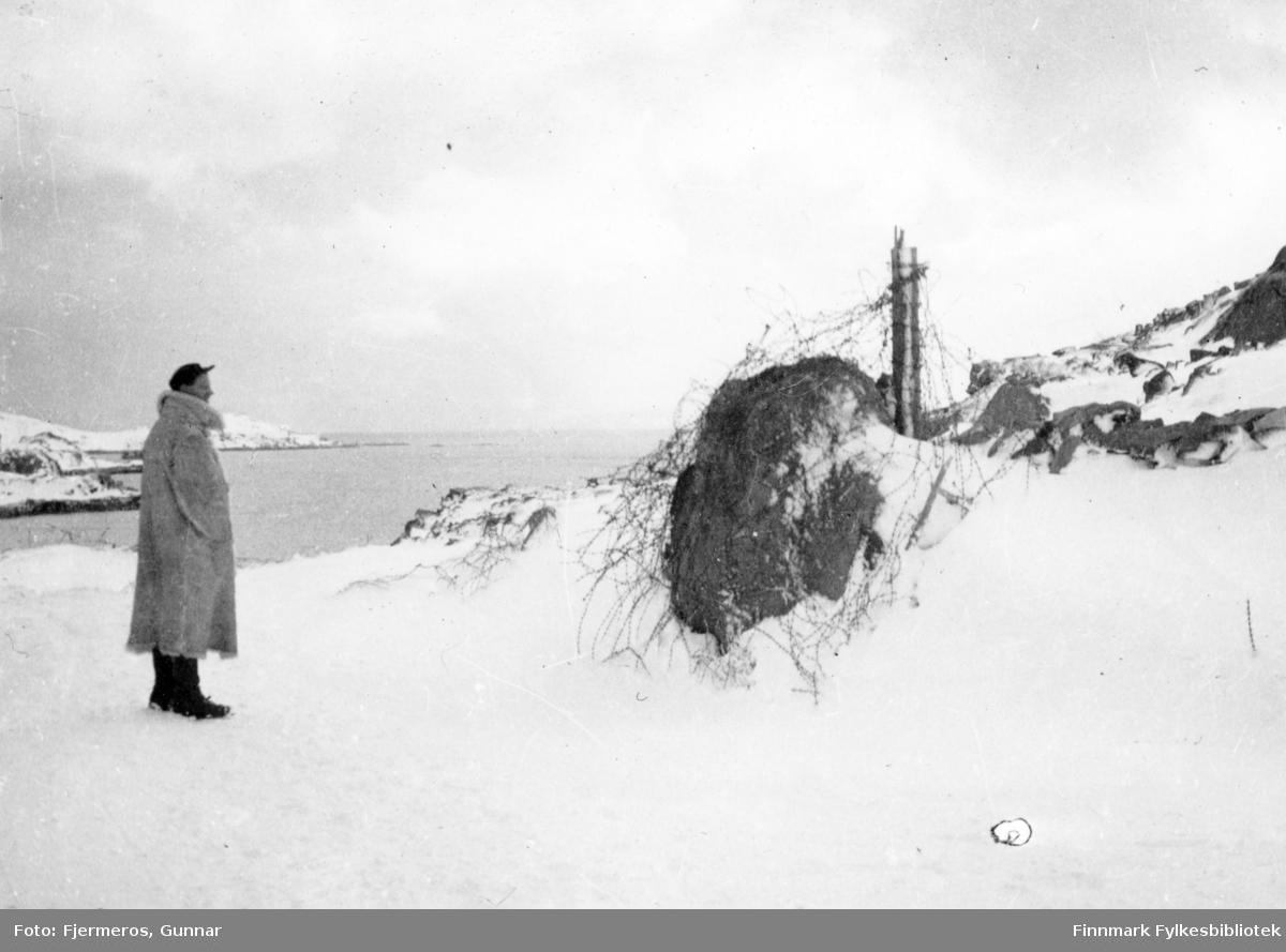 En mann står og ser på snødekte ruiner etter andre verdenskrig. Bilde tatt våren 1946. Person og sted er ukjent, men det kan være fra Honnigsvåg.