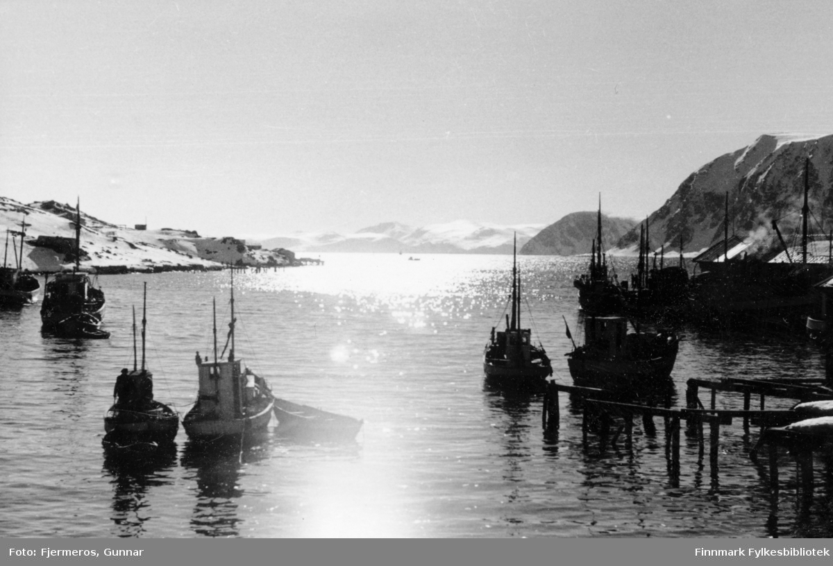 Sola speiler seg i sjøen en sen viterdag. Flere båter ligger fortøyd i havna og en del snø ligger i terrenget. Stedet er ukjent, men det kan være fra Honningsvåg.