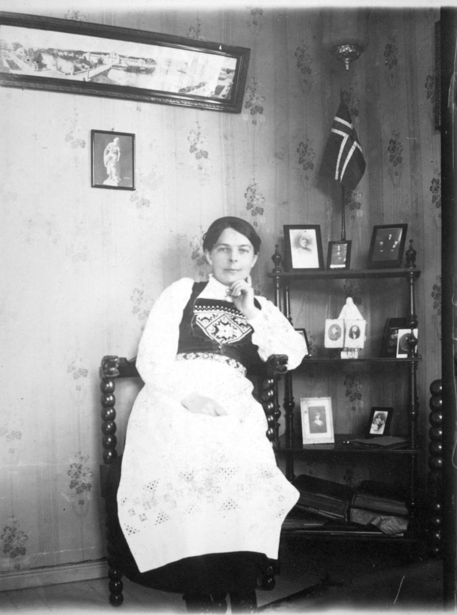 Mally Håheim sitter i en stol. Hun er kledd i bunad og bak henne kan man se en hylle full av fotografier og et norskeflagg.