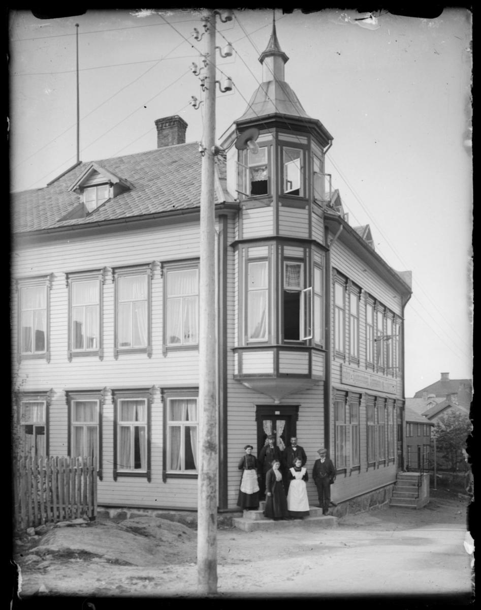 Reisen nordover november 1912. En gruppe mennesker utenfor en bygning.