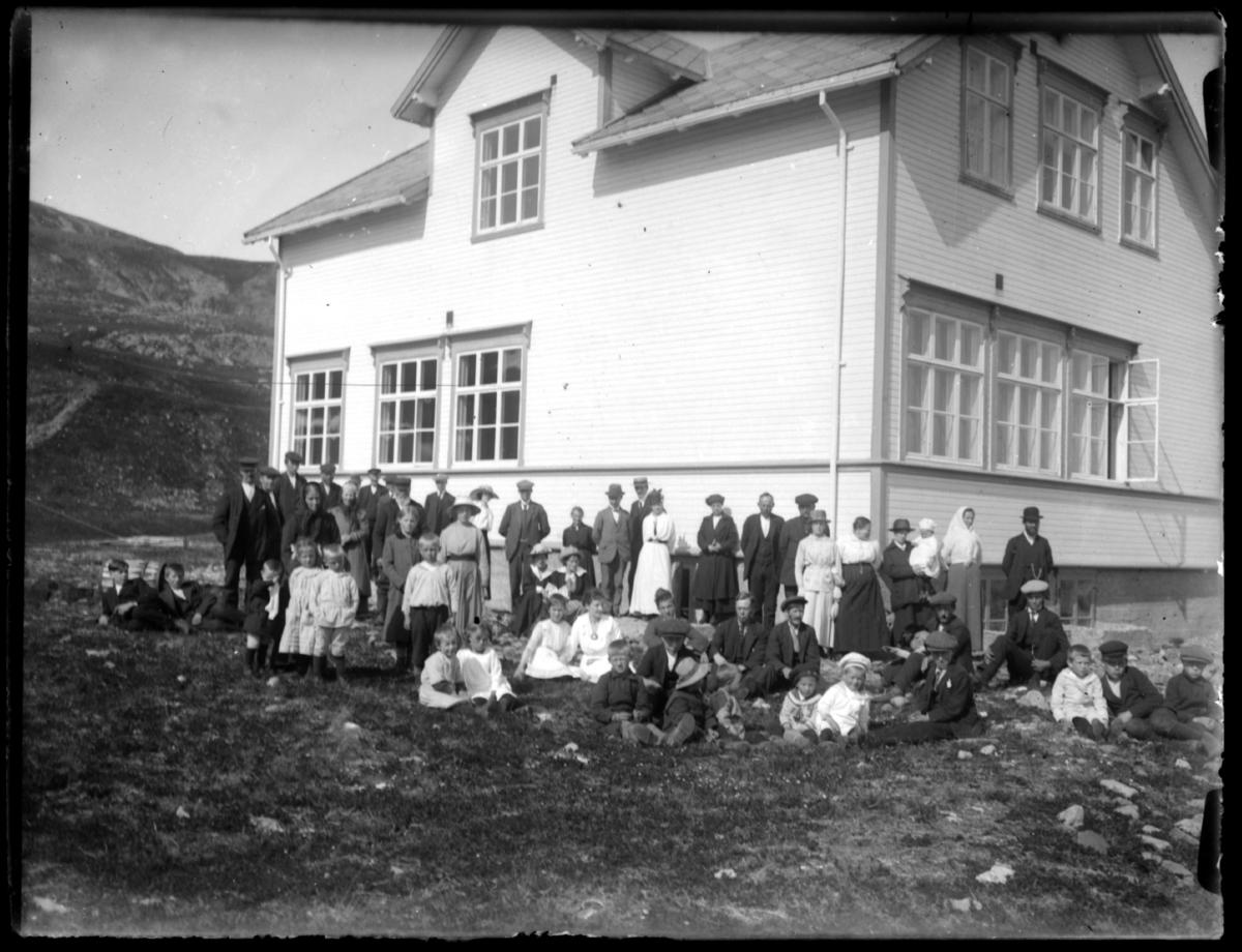 Gruppebilde ved det nybyggde kapellet ( brukes som kommunal ungdomshus nufortiden). En del av befolkningen fra Båtsfjord kledd i finstas har stilt seg for fotografering i en vakker sommerdag.På forgrunnen sitter mange barn, både gutter og jenter.  Samme motiv som fb.83327-038. Kapellet eies i dag av Båtsfjord Sportsklubb (BSK) fotball.