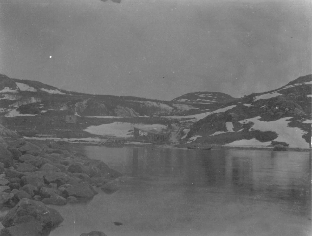 Bilde av ukjent vann. Langt bak i midten er det en foss, og en liten brygge eller lignende. En mann kjører i en liten båt mot høyre i bildet.