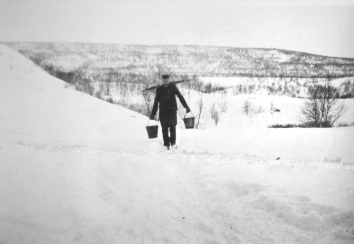 """""""Lars Bønå bærer vann fra Luftjokelva opp til huset sitt. Tunge tak og bratte bakker måtte forseres. Foto 1938."""""""