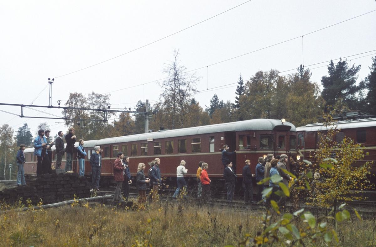 Ekstratog for Norsk Jernbaneklubb krysser persontog i Sandermosen. De reisende jernbaneentusiastene har tatt oppstilling for å fotografere det kryssende tog.