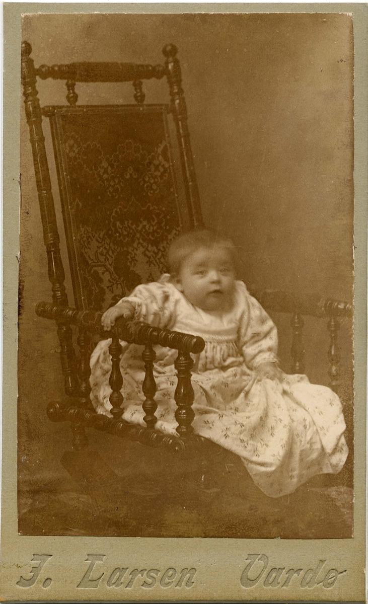 et lite barn sitter i en stol.