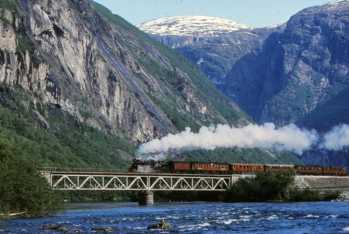 """Ekstratog """"To Hell with Steam"""" for Frank Stenvall, arrangert av Norsk Jernbaneklubb, med damplokomotiv 26c 411 passerer Foss bru over elven Rauma, ved km. 426,37 på Raumabanen, på vei fra Åndalsnes til Hamar."""