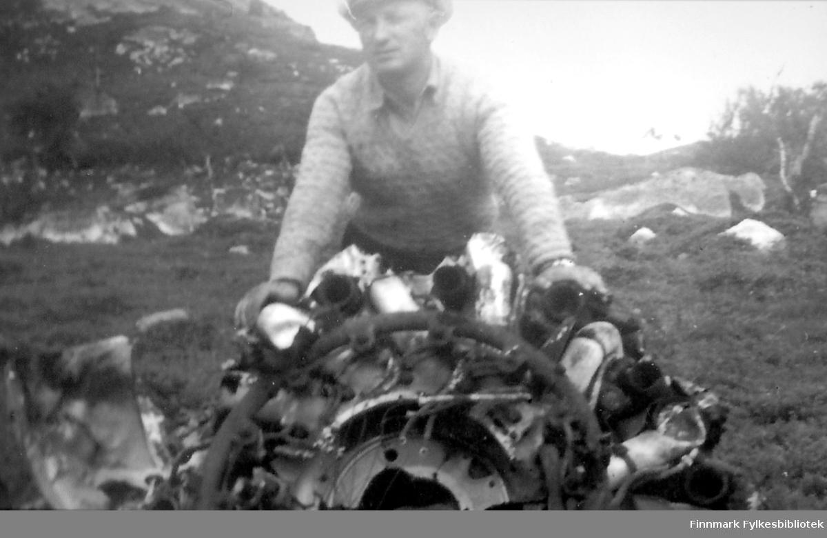 Nils Klaussen holder opp vrakrester av et fly. Bildet er tatt ved Jarfjord/Kirkenes ca. 1952/53. Rester av et flyvrak lå strødd rundt i området. Ifølge Inger-Lill Knutsen var disse restene etter et russisk fly som ble skutt ned i området under krigen.