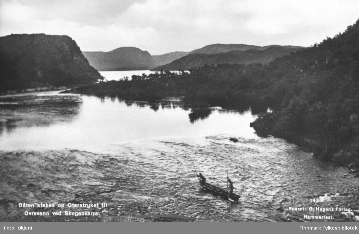 'Båten stakes op Oterstryket til Øvrevann ved Skoganvarre' står det trykket på dette postkortet. På bilde kan man se to menn i en robåt. De holder begge årer i hendene. Rundt vannet kan man se skog og fjell.