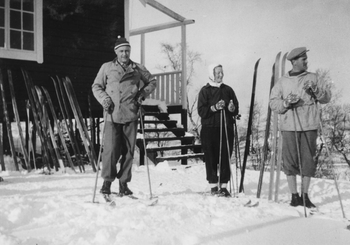 Harry Strand, Rachel Strand og ukjent på ski. Hytte i bakgrunnen.