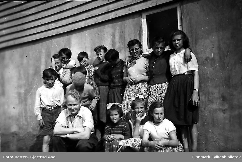 Elevene ved Smalfjord skole fotografert ved skoleveggen en solig dag i 1956 eller 1957. Barna er i forskjellig alder, alle er kledd i lette sommerklær, (skolestart ?). Jenta som sitter til høyre for læreren, er antakelig Astri Dalsbø.