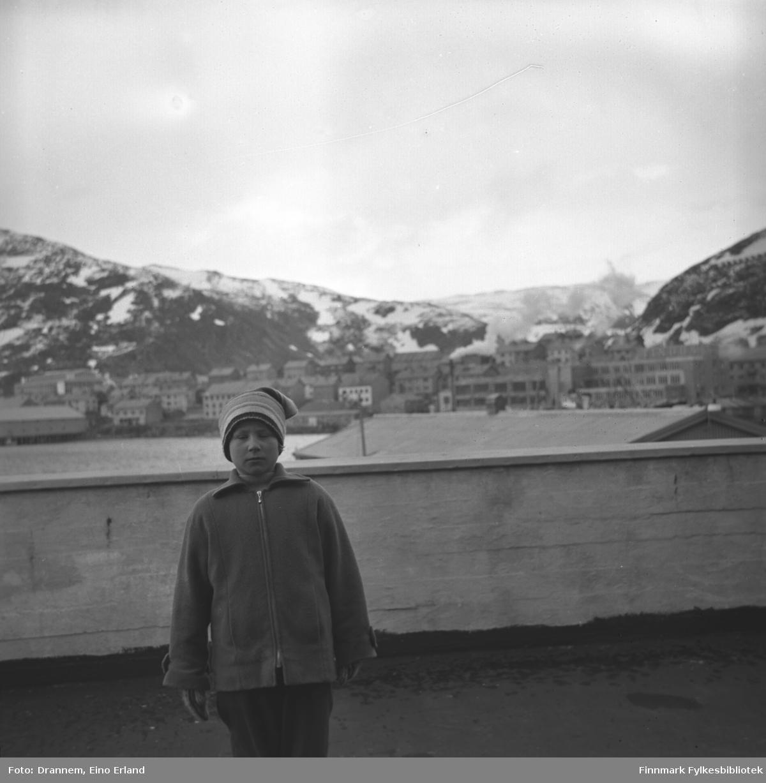 Turid Lillian står foran et gjerde. Bygninger og fjell i bakgrunnen