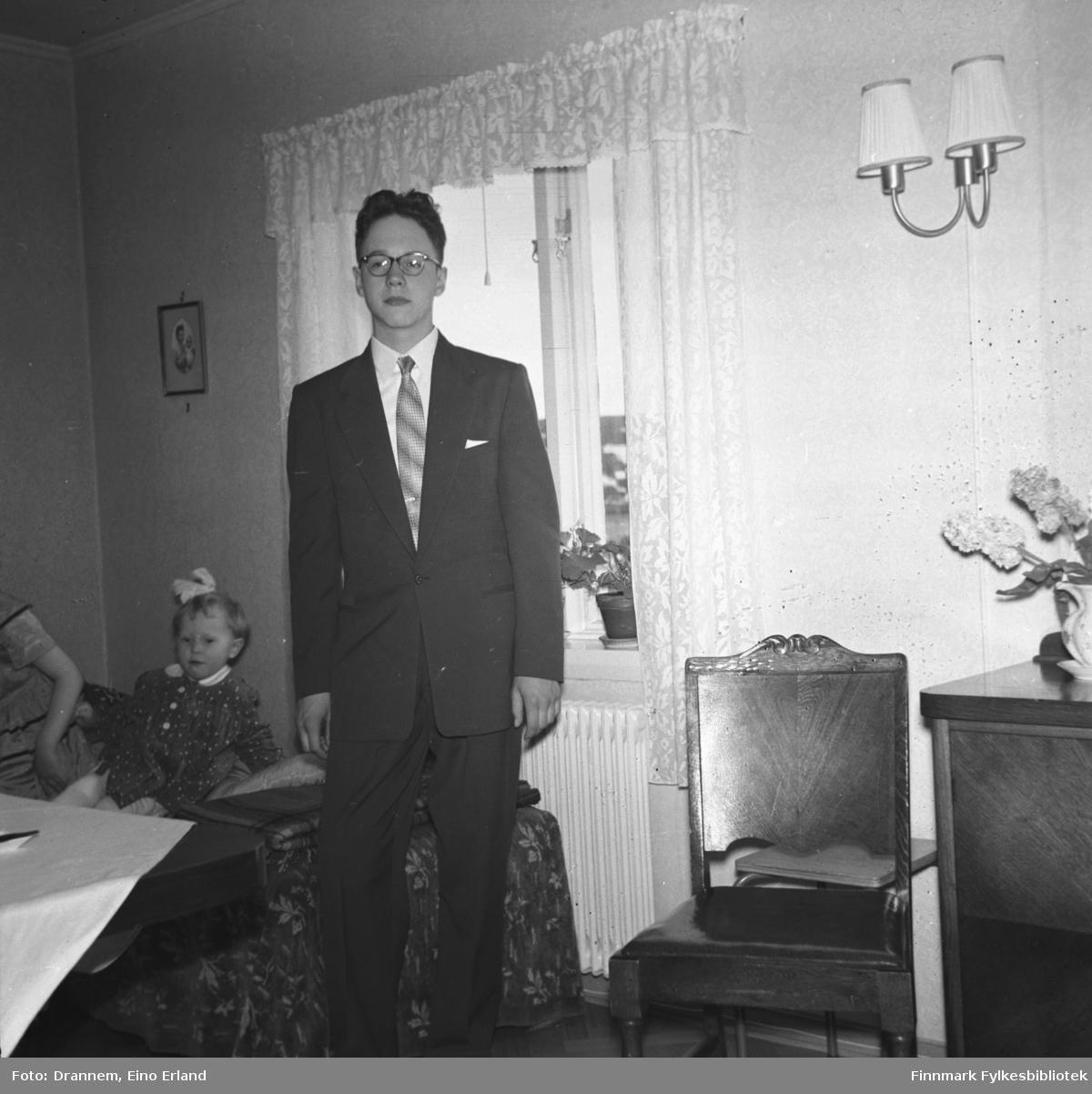 Arvid Sørensen, konfirmant ca. 1950, i stua til familien Drannem i Hammerfest på 17. mai. Grete Sørensen sitter på sofaen i bakgrunn.