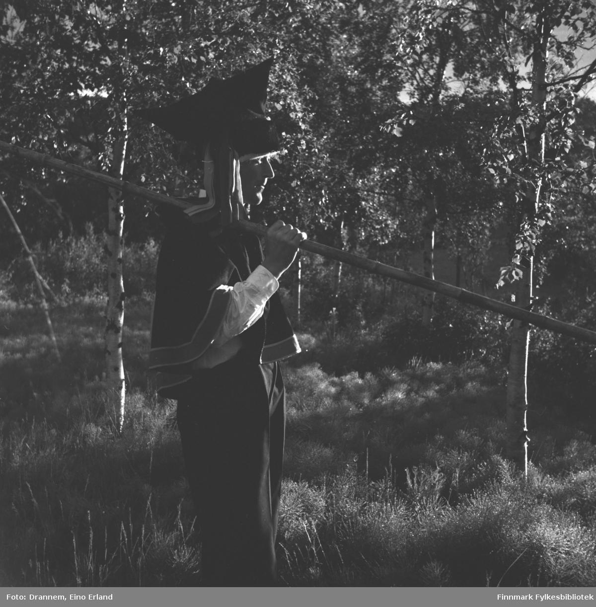 Olav Gabrielsen kledt i pesk og stjernelue, holder en lang stav i hånden (fiskestang?)