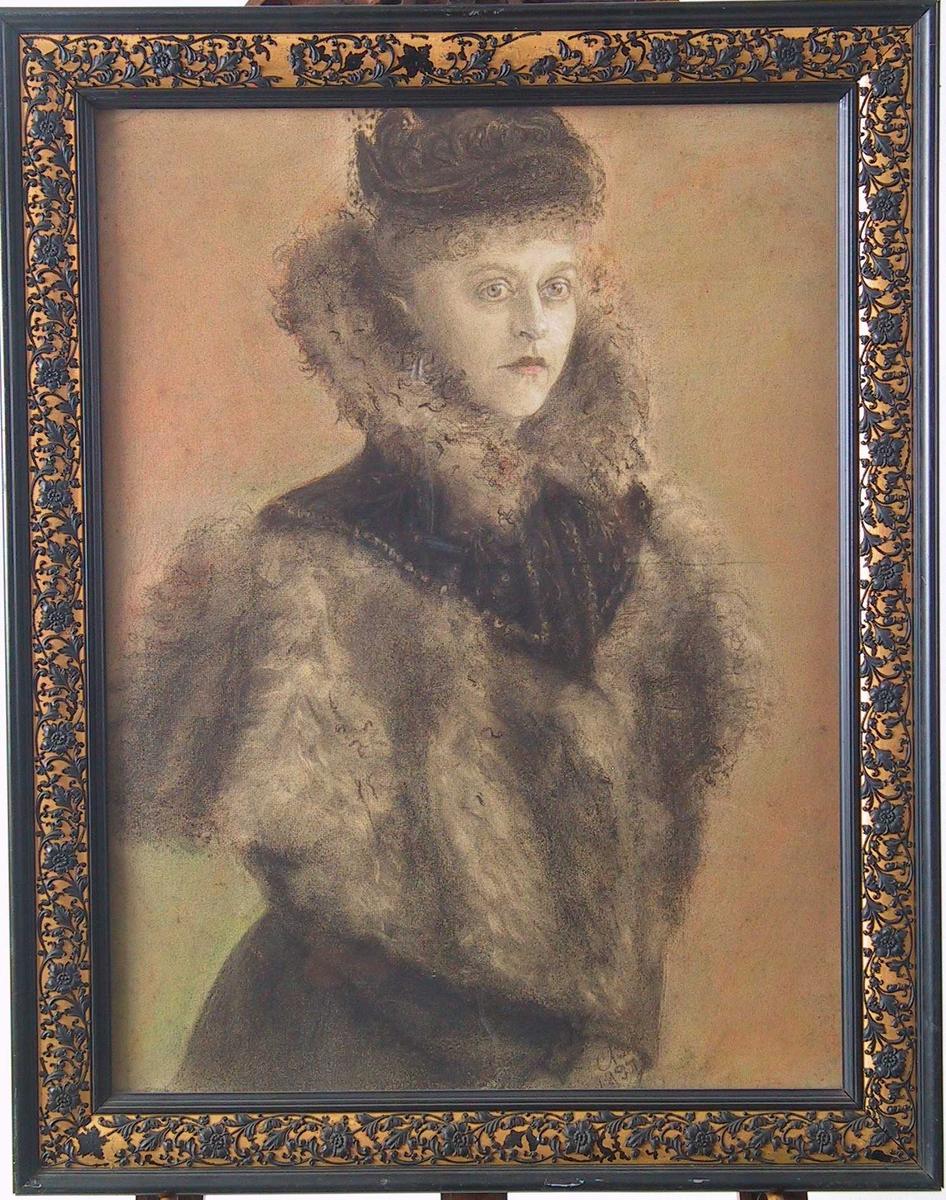 Stående kvinne, avskåret over hoftene, halvt høyrevendt.  Kledd i sort drakt med bred pelskrage i spiss pelskrage. Liten sort hatt med slør.