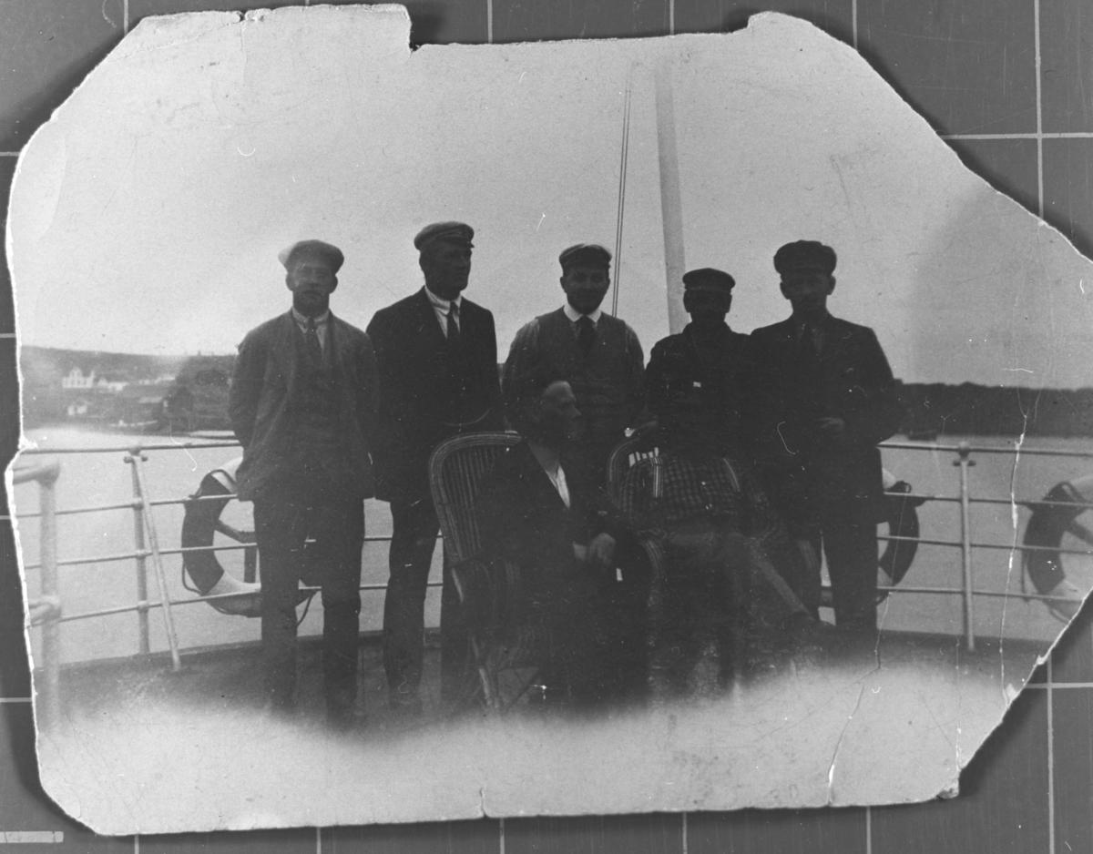 Gruppebildet er tatt av 5 mannssangere ombord i en båt ( muligens hurtigruta) på Berlevåg havn. Foran de 5 sitter det 2 stykker i hver sin stol. I bakgrunnen skimter vi Iversen-gården. Bak fra venstre Trygve Daldorff, Rolf Fredriksen, ukjent, ukjent, Margido Daldorff. Personene foran er ukjente.