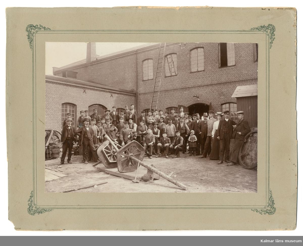 Motivet visar en gruppbild med arbetare på Kalmar Verkstad AB, Kalmar. I förgrunden två stora femkantiga hjul, i bakgrunden industribyggnaderna. En av personerna är givarens morfar Carl Moberg som arbetade som modellsnickare, han sitter i mitten lite till vänster, har hatt, vit skjorta och väst. Fotot är taget omkring 1920.
