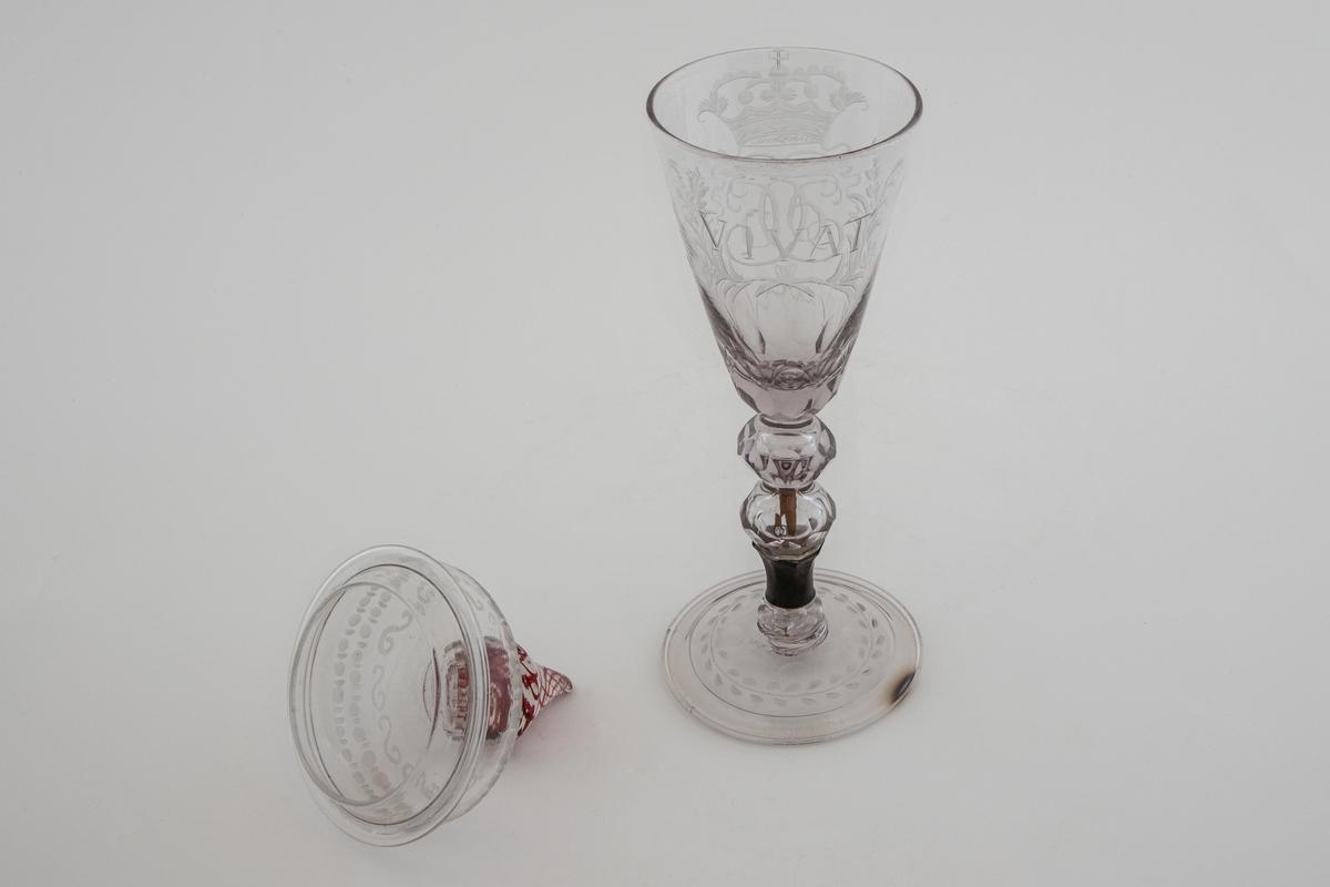 """Pokal med lokk i klart glass. Konisk kupa som er gravert med kong Christian VIs bekronede speilmonogram, omgitt av en krans. På baksiden av kupa er det gravert innskriften: """"VIVAT"""". Nedre del av kupa samt den flerleddede kuleformede stetten er dekorert med fasettsliping. Hevet sirkulær fotplate som er dekorert med olivensliping og gravering, sistnevnte i form av stilisert rankeornament. Sylinderformet hevet lokk, dekorert med graveringer i form av border med et eggstavlignende ornament og s-former. Dråpeformet lokknapp med røde innlagte emaljetråder i spiralbevegelse."""