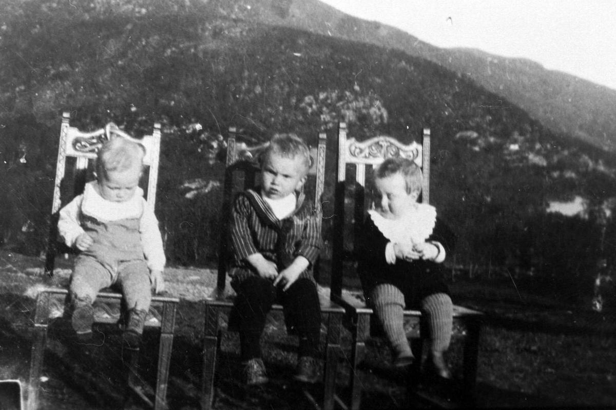 Amatørportrett av tre små gutter som sitter på hver sin stol utendørs.