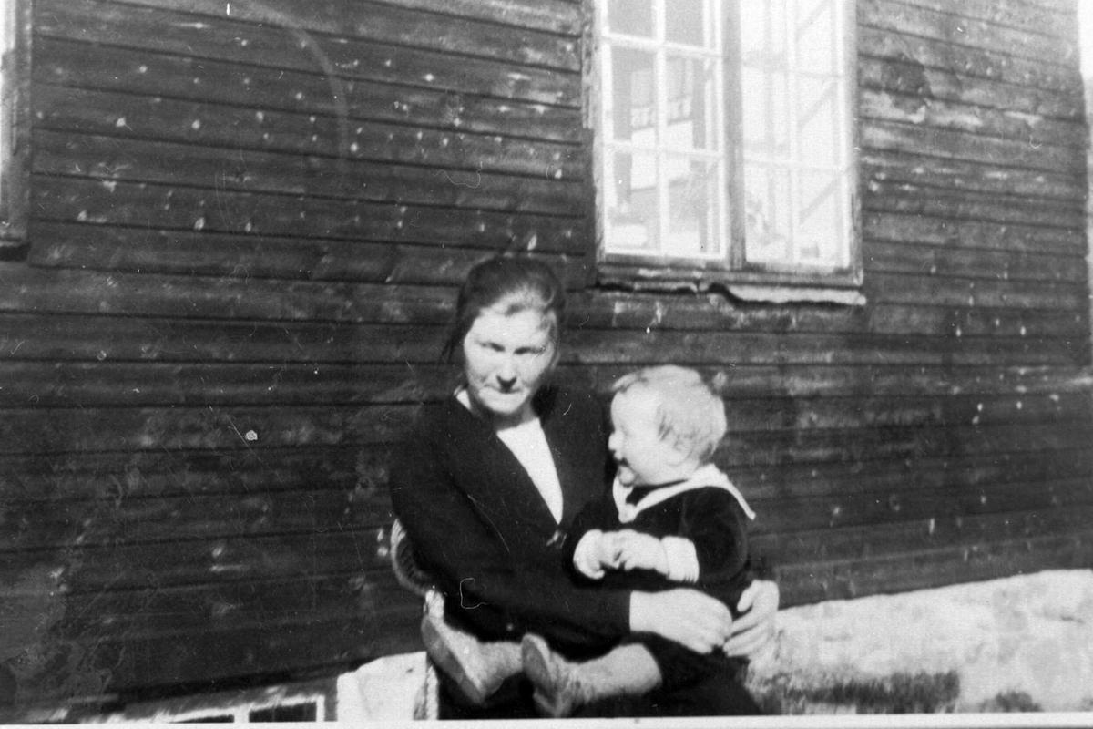 Amatørportrett av kvinne med barn på fanget sittende på stol foran en husvegg.