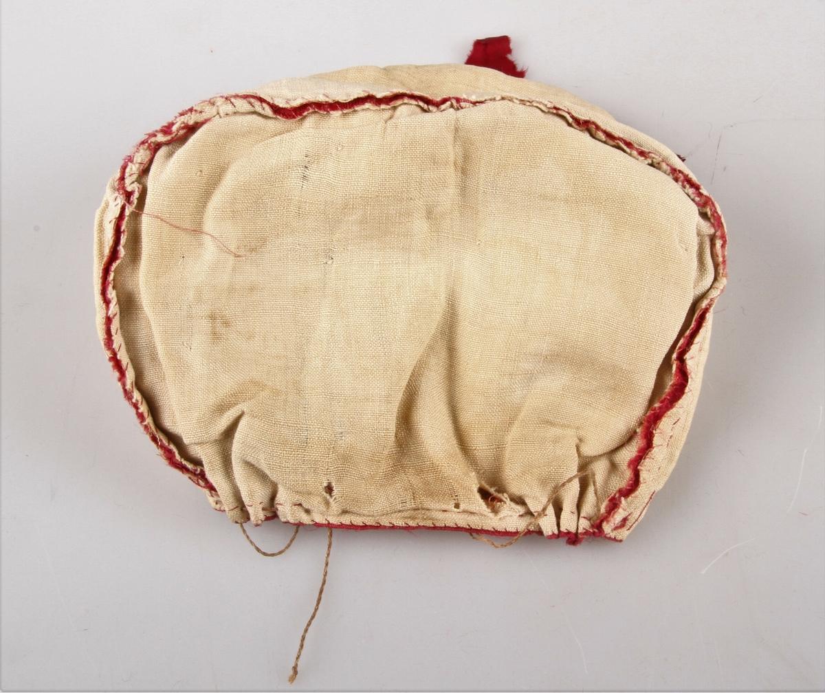 Kvinnelue i kaminrød natursilke. Lua er foret med et lerretsvevet linstoff, og kantet med gullkniplinger. Knytebånd av rød natursilke. Lua er sydd sammen av to stykker, en noe avrundet pull i nakken, rynket med rynketråd i lin, og et pannestykke som går fram i en liten spiss i pannen. Hele lua er sydd for hånd med naturfarget og rødfarget lintråd.