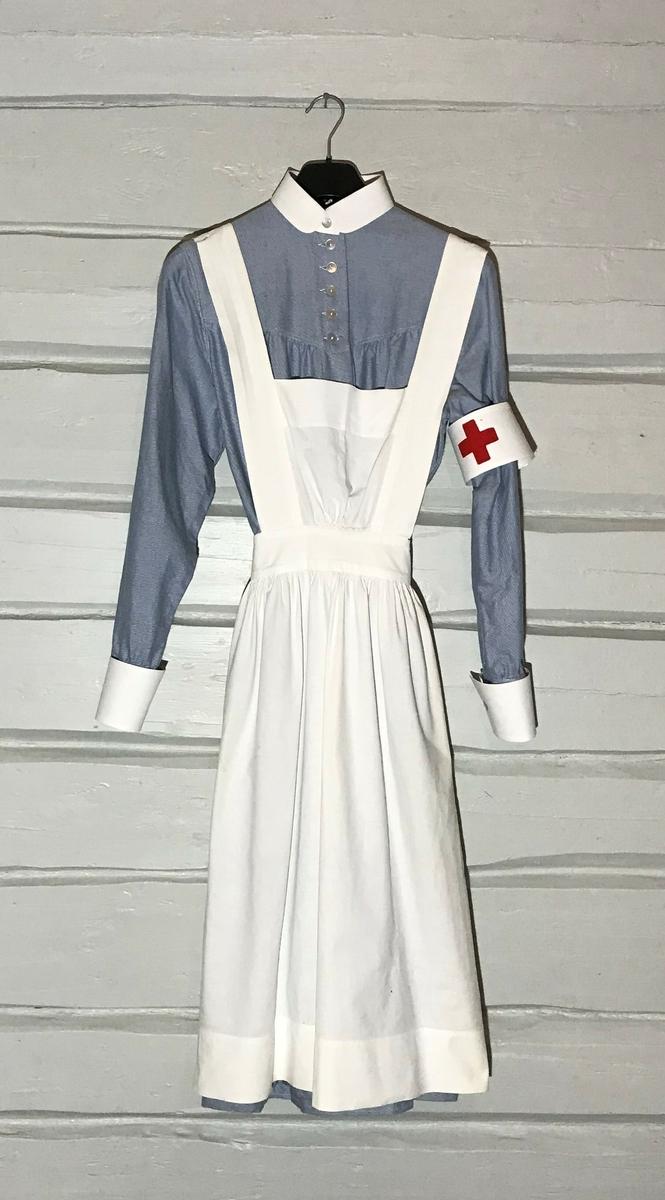 Uniformen består av kjole, forklede, 2 mansjetter, 1 armbind med rødt kors, krave og lue